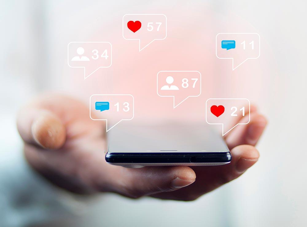 Roka, kas tur mobilo telefonu. Redzamas sociālo tīklu ikonas ar sekotāju skaitu, ziņu skaitu un like skaitu.