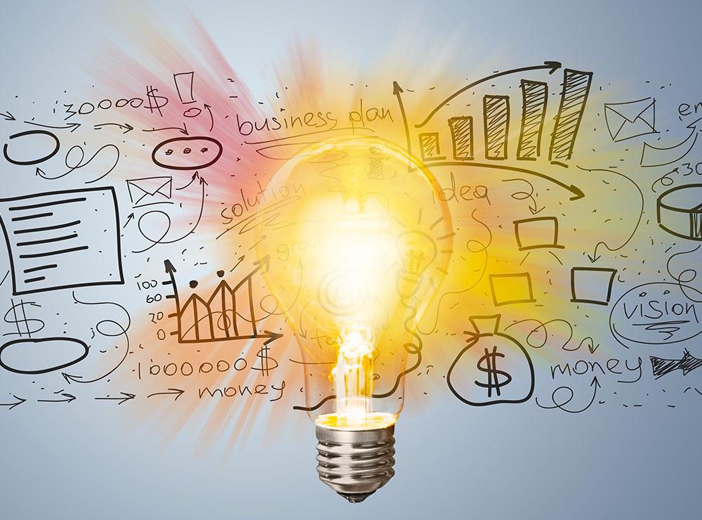 Pieraksti ar dažādām idejām, vārdiem un skicēm. Un centrā idejas simbols - ieslēgta spuldzīte.